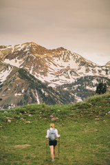 A woman hikes out towards a ridge and a mountain with warm sunset light.