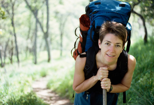 Female packpacker leaning on a hiking staff in California.
