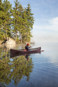 A fisherman casts a fishing line during a cool autumn morning in Vermont.
