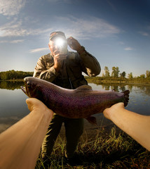 A person showing a trout to a friend.