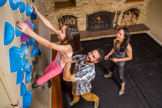 High Angle View Of Family Playing On A Climbing Wall In House
