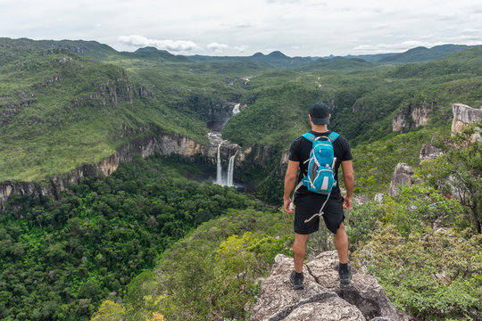 Young adult hiker on rocky edge looking at beautiful cerrado landscape with waterfalls and river in the green forest, Mirante da Janela peak, Chapada dos Veadeiros, Goias state, central Brazil