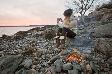 A woman takes a cell phone picture of a sunset along the Maine coast.