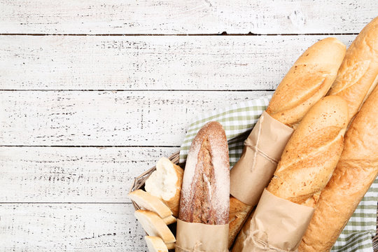 Fresh baguettes with napkin in basket on wooden table