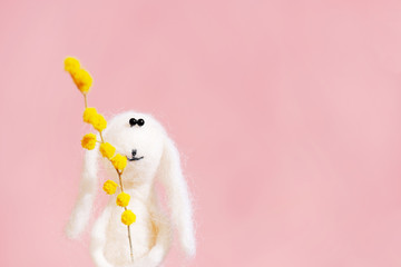Cute toy bunny with flower of mimosa congratulate on Easter