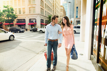 A cute young couple with their luggage walks side by side on a footpath in Dallas.