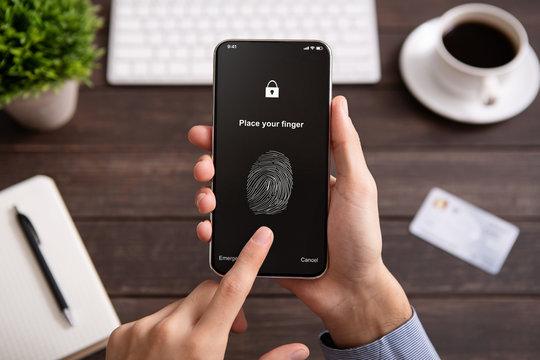 Hand holding mobile phone with application for scanning fingerprint