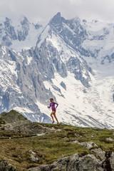 Girl trail running in Chamonix around the Chesery lake