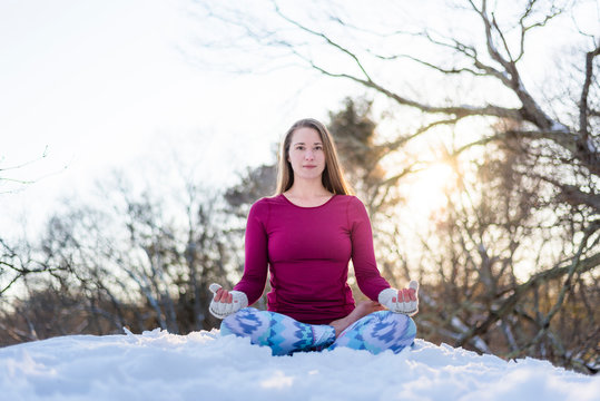 Portrait of woman in lotus position while doing yoga during winter