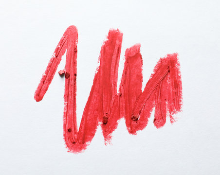 Red lipstick smear on white background, top view