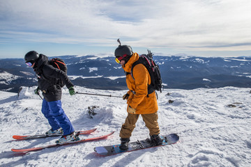 Skier helping a snowboarder to gain speed on a flat part