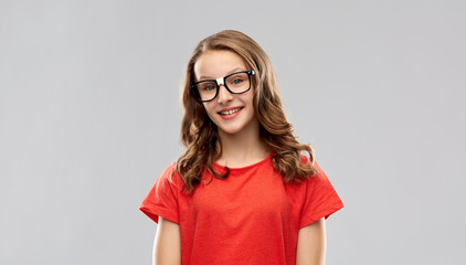 education, school and people concept - smiling teenage student girl in glasses and red t-shirt over grey background