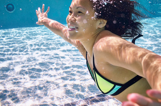 A young Asian American woman enjoys a summer day at the pool.