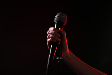 Woman holding microphone on black background, closeup