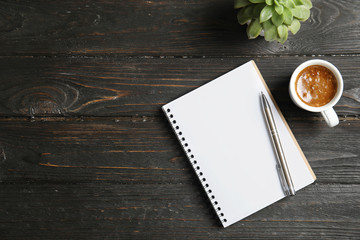 Notebook, coffee and plant on dark wooden background. Space for text Wall mural