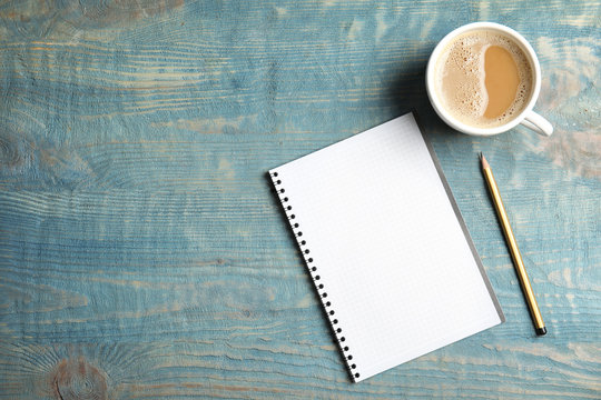 Notebook and coffee on wooden background, top view with space for text