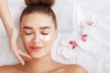 Under eye treatment. Woman with patches, relaxing in spa center