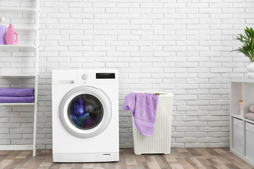 Modern washing machine near brick wall in laundry room interior, space for text