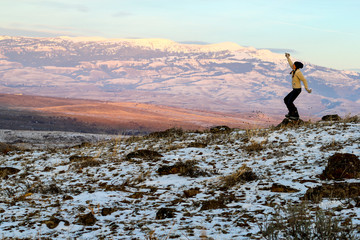 Woman fist pumps her hands in excitement in the mountains