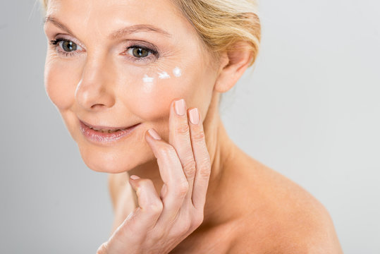 beautiful and mature woman looking away with cosmetic cream on face