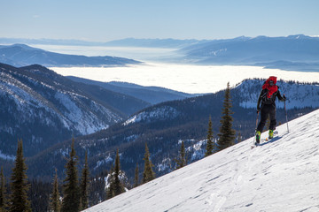 A backcountry skier tours through the Rattlesnake Mountains high above an inversion in the Bitterroot and Missoula Valley, Montana
