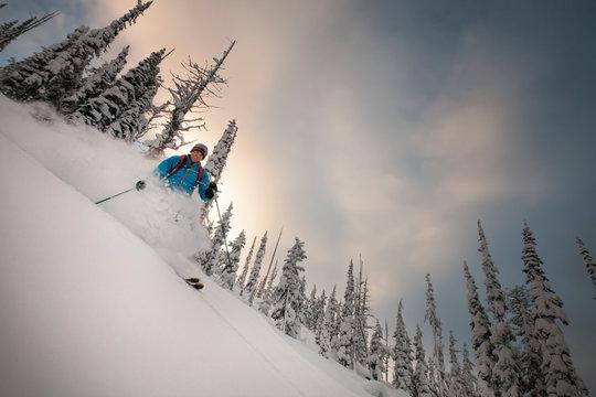 A man back country skis powder at sunset at Lolo Pass near Missoula, Montana.