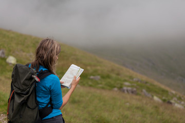 Female hiker consults map for direction