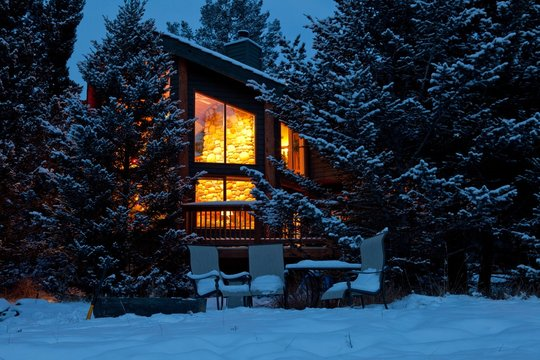 Illuminated home in snow forest