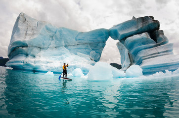 Man on stand up paddle board against iceberg