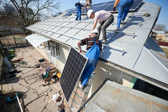 Male team workers installing stand-alone solar photovoltaic panel system. Electricians lifting blue solar module on roof of modern house. Alternative energy ecological concept.