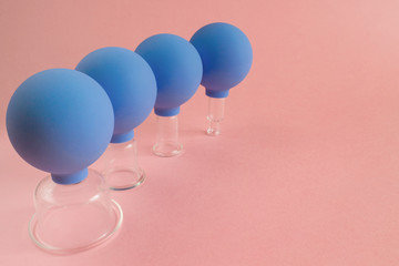 four blue cosmetic vacuum jars of different sizes made of glass and rubber on pink background.