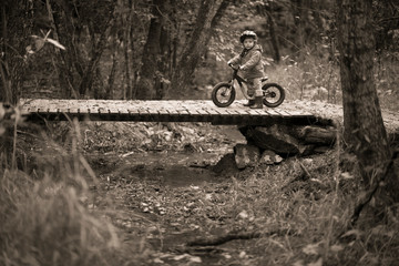 Baby boy with bicycle on footbridge in forest, Rancho Santa Elena, Hidalgo, Mexico