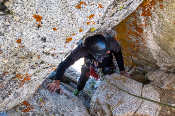 A Man Squeezes Through A Hole In The Rocks On Climbing Route Located On Utah's Wasatch Mountains