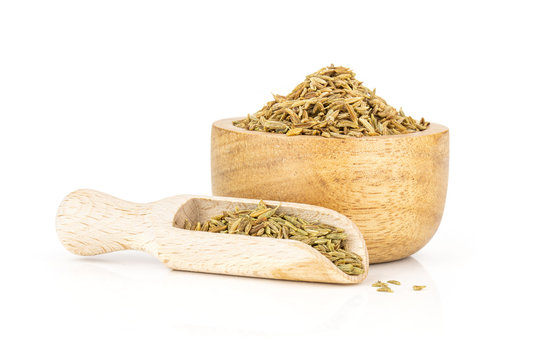 Lot of whole roman caraway seeds in a scoop with wooden bowl isolated on white background
