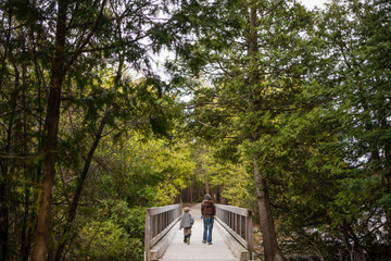 Mother and little son walking across Georgian Bay wooden bridge