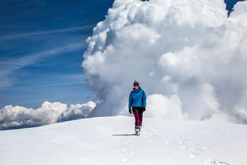 Woman walking on snowy summit of Mt Adams, USA