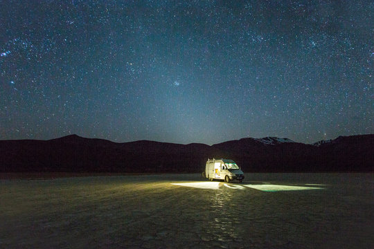 ALVORD DESERT, HARNEY COUNTY, OR, USA. A white van is parked in a giant dried lake bed at night under a starry, Milky Way sky with what appears to be a halo of light around the van.