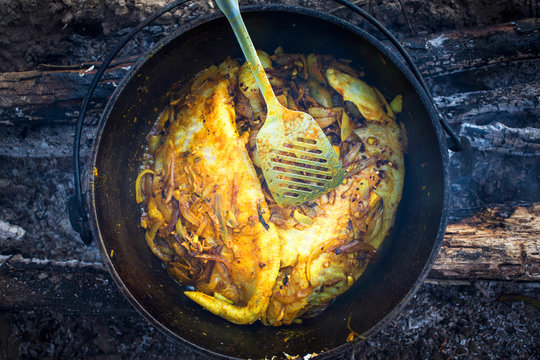 Atchafalaya River, Louisiana, USA. Looking down on catfish cooking in a black cast iron pot over a wood fire.