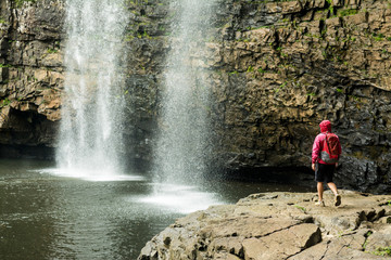 A woman hikiing below waterfall in Fall Creek Falls State Park, Pikeville, Tennesee.