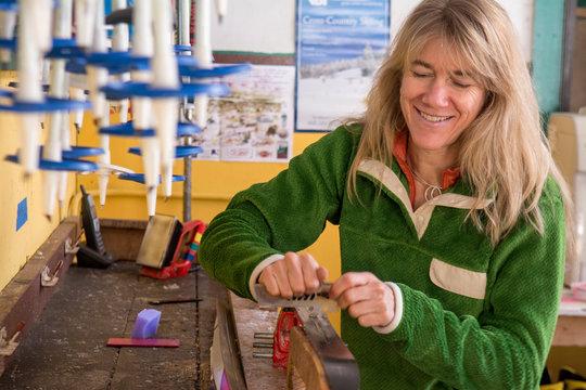 A woman waxing cross country skis at the Nordic Center near Durango, Colorado.