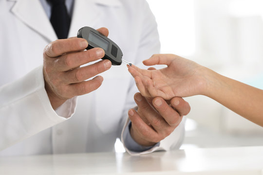 Doctor checking patient's blood sugar level with digital glucometer at table, closeup. Diabetes control