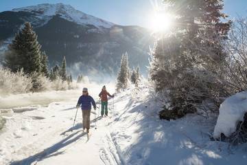 Two girls skiing in forest
