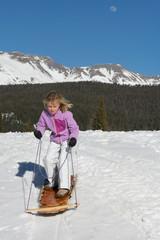 Girl sledding in mountains, Silverton, Colorado, USA
