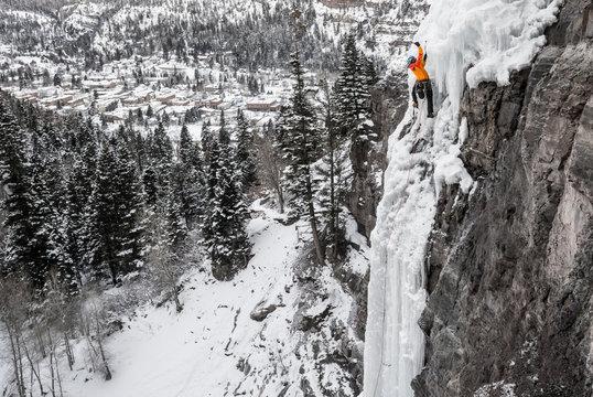 Man climbing on frozen waterfall in winter