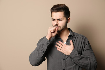 Handsome young man coughing against color background. Space for text