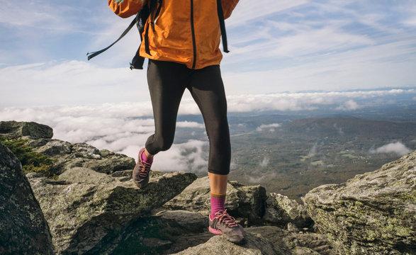 Woman hiking on a rocky ridgeline in New England.