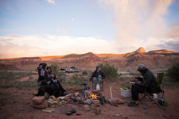 Group of people sitting around campfire in Moab, Utah, USA