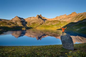 Hiker standing on boulder on shore of Ice Lake, Silverton, Colorado, USA