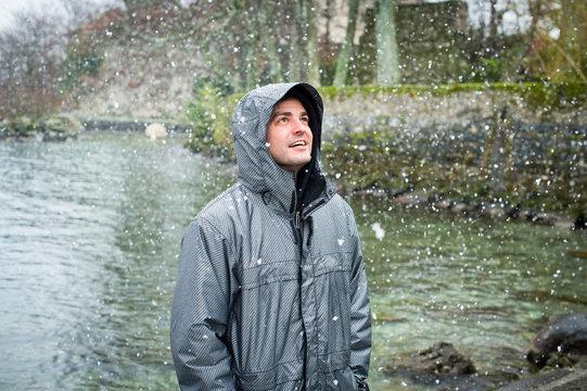 Man staring at snow flakes near river