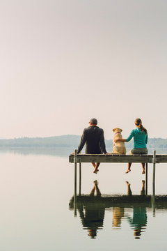 Woman, dog and man relaxing on the end of long lake dock.